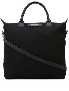 Black organic cotton O'hare tote bag from WANT Les Essentiels featuring a rectangular body, round top handles, a detachable shoulder strap, a top zip closure, a main internal compartment and a front logo patch. Please note this item is unisex. Black Tote Bag, Shoulder Strap, Shoulder Bags, Cotton Tote Bags, Leather Handle, World Of Fashion, Luxury Branding, Round Top, Organic Cotton