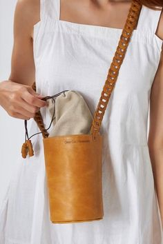 An update to our favorite Roxanne, this bag is reimagined in a mini version with our signature woven slim strap. It is handmade of top quality leather that comes in camel (waxed nubuck), black, white and taupe canvas with a drawstring closure. Carry it on your shoulder or wear it crossbody, the days you want nothing to weighing you down. It can hold your sunglasses, cell phone, keys and card-wallet. Greek Chic Handmades Women's bags are designed and handcrafted in Athens, Greece. Black Leather Crossbody Bag, Leather Shoulder Bag, Shoulder Bags, Shoulder Strap, Leather Bags Handmade, Women's Bags, Tote Bags, Crossbody Bags, Card Wallet