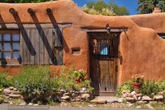 Adobe House, Santa Fe. Scraggly green plants. Weathered old door. Fantastic photo.