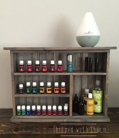 Essential Oil Storage Shelf   This is the perfect way to display your Essential Oils while keeping them safe and organized. Our design features an arrangement of shelving that will fit all of your oil bottles and supplies. The shelves are deep enough to comfortably accommodates 3-4 5ML YL bottles or 2-3 15ML YL bottles.  This shelf comes stained in a grey finish and sealed with a clear coat to ensure its beauty for years to come. Approximant cabinet dimensions: AT WIDEST POINT 17 H 24 W 4.75…