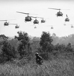 Helicopters over grassy field in Vietnam