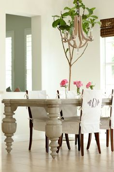 elephantitis of the table leg - and the tree and chandelier are stupid too - and i don't like monogram chair covers - it's all bad - even the flowers - and that bamboo shade doesn't work in there