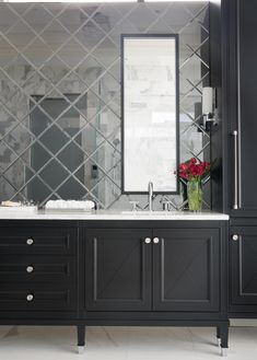 The homeowners wanted a dramatic and luxurious look, but also functionality. The custom vanity features a neoclassical style, while concealing the power for blow dryers and curling irons. Beveled diamond-shaped mirrors are used to create a sophisticated backsplash.