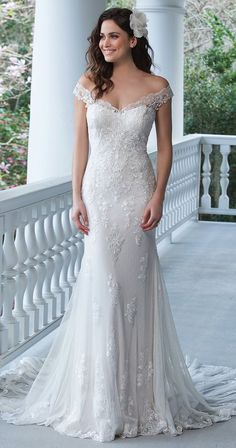 Show off your shoulders in this fit and flare tulle and point d'esprit gown with lace appliques, illusion back, and Jersey lining complete with a chapel length train.