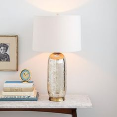 "$169 14""diam. x 27""h. Antiqued mercury glass base with Antique Brass-finished accents. White linen shade with a Champagne metallic interior. Louise Table Lamp #westelm"