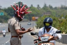 Police officer Rajesh Babu, wearing a helmet depicting coronavirus, requests a commuter to stay at home in Chennai, India, March REUTERS/P.