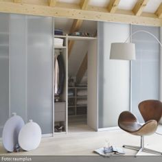 Die sonst eher unbeliebten Ecken in Zimmern mit Dachschräge eignen sich gut für den Eibau eines begehbaren Kleiderschranks. Dieser begehbare Kleiderschrank mit Schiebetüren verwandelt den Raum in ein Zimmer zum Relaxen.