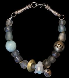 Necklace by Marion Hamilton - composed of antique beads: Clear Dutch Dogans make up the large part of this piece. Silver fish from a Yemeni necklace form the clasp, and a Brazilian aquamarine ring, a brass Ethiopian ring and a seed fetish add interest. A moon bead and an antique Nigerian bead are at the sides.
