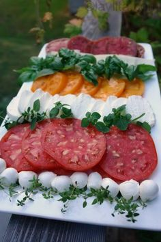 Easy tomato appetizer platter made with ripe tomatoes, your favorite cheeses, and herbs like fresh basil, oregano and thyme, served with olive oil, balsamic vinegar and bread.