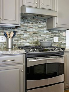 Think Green--use recycled glass tiles that play up the kitchen's color...I like the gray colored cabinets