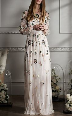This **Needle & Thread** dress features a jewel neckline, sheer long sleeves, lace detailing, full floor-length skirt, and finished with hand embroidered multicolored sequins and beads arranged in a floral motif.