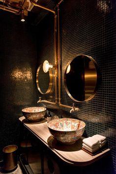 foorni.pl | Restauracja Bibo – czarno-złota mozaika, czarna mozaika ze złotym połyskiem, kolorowa umywalka na drewnianym blacie, okrągłe lustro w złotej oprawie
