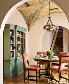 The breakfast room holds a custom table and chairs in a Schumacher fabric; the clients' mahogany breakfront was painted blue-green to set off their pottery.   - HouseBeautiful.com