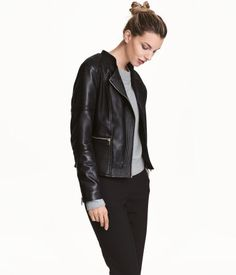 Black. Fitted biker jacket in imitation leather with quilted details. Stand-up collar with wide lapels, diagonal zip at front, side pockets with zip, and