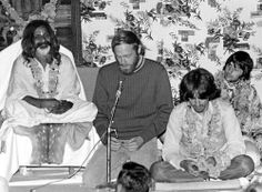 Maharishi Mahesh Yogi with the Beatles George Harrison and Ringo Starr and Mike Love from the Beach Boys speaking into the microphone .