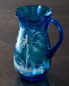 *BLUE PITCHER ~ c. 1880. Mary Gregory turquoise glass pitcher w/ rippled lip depicts a boy sitting in a tree. Except for the fruit on the ground + the clusters of fruit in the tree, the design is rendered in white. The pitcher has a sharp edge where the handle is applied + another on on the bottom where the pitcher was detached from the rod used in its production. These edges are consistent with handmade glass.
