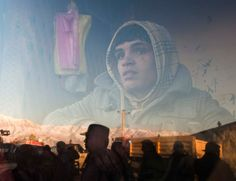 An Afghan boy who works at a bakery watches a protest outside his a window in Kabul Feb. 24.