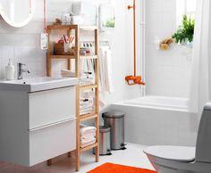 ห้องน้ำตกแต่งด้วยเครื่องสุขภัณฑ์และกำแพงสีขาว ชั้นวางของทำจากไม้ของอิเกีย และฝักบัวสีส้ม