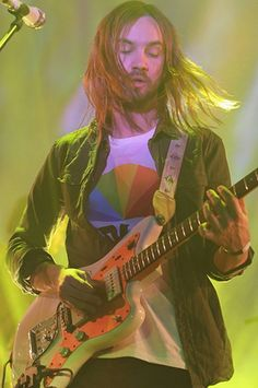 Tame Impala's Kevin Parker wears khaki open shirt with t-shirt on stage