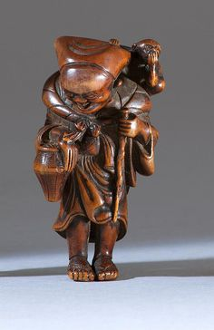 WOOD NETSUKE Depicting a sarumawashi entertainer with his monkey. Height 2.3""