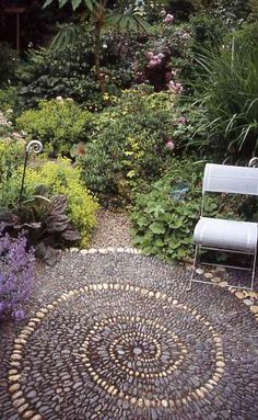 spiral pebble patio - maybe not spiral, but I do like the pebble pattern idea. Might be a good idea instead of cement.