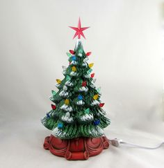 Very detailed hand painted medium ceramic Christmas pine tree with a beautiful intricately designed red base and with a light kit Very high quality - painted to last. Tips of branches painted with white to resemble snow and a light dusting of glitter and subtle gold adds the finishing twinkling snow effect. Comes with a light kit, lights and star. Colour of star may vary. Extra lights will be included in case of loss. Easy to assemble - the lights and star are delicate and so we provide them…