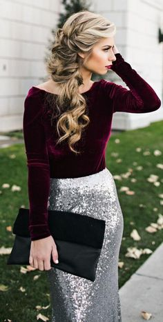 Burgundy long-sleeve velvet blouse, chestlength dark-rooted blonde spirals, red wine lips, black clutch w/ velour flap, silver  sequined skirt; strip of lush green grass