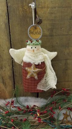 A sweet and sparkly angel! She has sparkly wings and a crown of faux berries and evergreen that sparkle, as well as the star she holds. She is made of homespun and warm and natural. She has wire arms that hold a star. A wire above her head holds a rusty bell and a Believe tag. She will look truly angelic on your tree and would make a lovely gift for someone special! She is about 7.5H X 4 3/4 W (wing tip to wing tip) X 2 1/4 D. For decoration only. Thanks for visiting