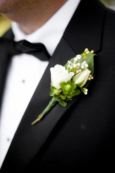 A tidy green and white boutonniere brightens a groom's lapel. #Weddings