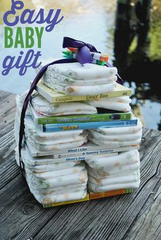 Need an easy and fast idea for a baby shower gift? Create this books and diaper tower using ribbon, diapers, and DVDs. No need to wrap this one!  #DIY #Baby #Shower #Gifts