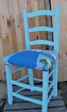 Silla antigua pintada en azul turquesa claro y tapizada en loneta estampada con motivos de montaña.    Serviría tanto para habitación juvenil como otro lugar.    El asiento es firme y estable.  Tamaño