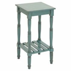 "Wood end table in blue with turned legs and a slatted bottom display shelf.  Product: End tableConstruction Material: WoodColor: BlueFeatures:Turned legsSlatted accents Open bottom shelfDimensions: 29"" H x 14"" W x 14"" D"