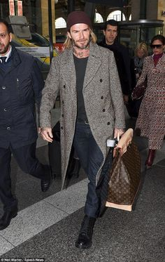 David Beckham wearing Louis Vuitton Black Ice Ankle Boot, Louis Vuitton Stretch Slim Jeans, Louis Vuitton Monogram Steamer Bag 45 and Louis Vuitton Garment Cover in Damier Graphite Canvas