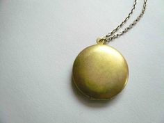 Vintage gold locket on long necklace chain. Simple and romantic brass circle locket.. $19.00, via Etsy.