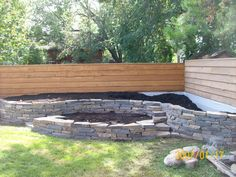 Another natural stone wall I built. I wasn't very particular about building up against a fence, but it still made for a nice two level garden. I always try to add in some stairs for a more interesting look. Easy access for working is important as well. visit www.dream-yard.com for landscaping how-to's, picture ideas, and articles.