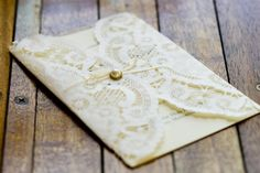 Envelope liner/letter surround DIY; get round paper doilies, square off the top/bottom in line with your invite, and use a gold brad with a small bow to fasten.