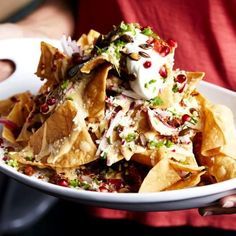 Legendary Nachos Recipe From L.A.'s Bar Amá -  a mountain of chips layered with mornay sauce, avocado salsa, crema, cotija cheese, sliced radishes, cilantro, pumpkin seeds, and even pomegranate