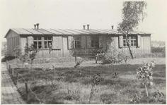 Anonymous | Een houten barak, Anonymous, 1940 - 1945 | Houten barak met een grasveld ervoor. Uit een raam kijkt een soldaat. Foto behorend bij album 'Kriegserinnerungen'.