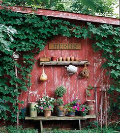 Love the re-use of old lumber stacked for a shelf, odd pots, old garden tools...just a beautiful scene.