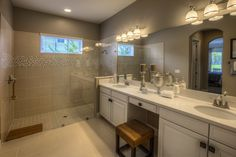 Frameless glass shower doors give your master bathroom a sense of infinite spaciousness. Seen in Oakland Park, an Orlando community.