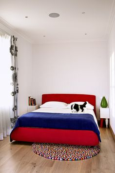The children's bedroom features clean white walls and a red double bed with a blue throw for an element of colour alongside the multi-coloured rug. The simplicity of the room is emphasised by the polished wooden flooring and the black and white, floor-length curtains. The bespoke ceiling lights are discreetly positioned to brighten up the area.  #bedroom #kidsbedroom #cushions #flooring #woodenfloor #curtains #lights #bedroomideas #childrendecor
