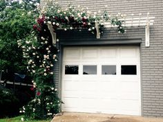 "This garage pergola with red & pink intertwined climbing roses adds interest to the street view of this Prairie style home. This trellis uses our new 12"" X 24"" bracket in the middle for extra support."