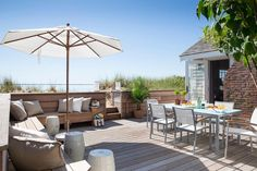 Chic teak deck features an L shaped built-in bench adorned with white and soft gray pillows as well as white stools shaded by a white folding umbrella.