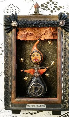 This shadow box is 8 tall. The Halloween Joker inside is made from an old perfume bottle, clock gears, chenille and I made his head from clay. He is