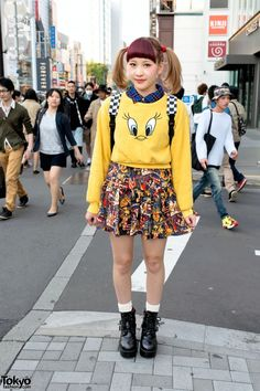 Ayaka is an 18-year-old girl with red bangs and cute twin tails who was met on the street near Kinji Harajuku. She works at a hamburger restaurant. Ayaka's look includes a Tweety Bird sweatshirt from Sevens over a plaid shirt, a Spinns graphic skirt (the print appears to be retro American propaganda posters), and platform boots. Her bag choice is a checked backpack. (Tokyo Fashion, 2014)