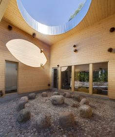 Omenapuisto Day-Care-Center / Hakli Architects, daycare courtyard, wood siding, round skylight