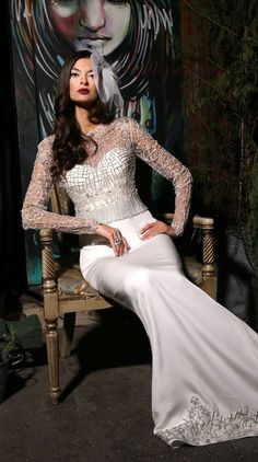 Crepe, fit and flare gown with corset style bodice. This gown is paired with a fully beaded and frindged long sleeve top.