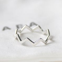 Simple and modern with unique design to the point is good. This ring will fit nicely with other rings you may have. And 92.5 Sterling silver