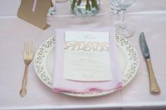 Mis en place con posate dorate, piatto bianco decorato in oro, tovagliolo rosa e menu su cartoncino bianco con dettagli oro
