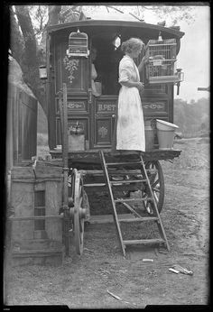 A young lady standing on the steps of a traditional style wooden caravan. She's tending to a parrot in one of the birdcages. From Arthur J. Fenwick (1878-1957) collection of circus material.